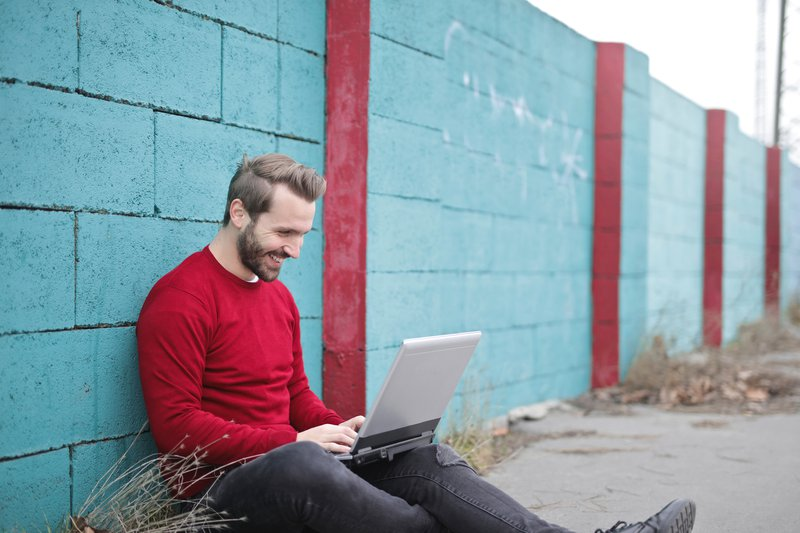 man-leaning-against-wall-using-laptop-941572.jpg