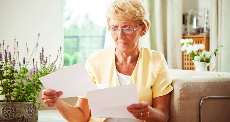wp-content/uploads/2015/11/solemn-senior-woman-reading-paperwork-in-living-room-mst.jpg